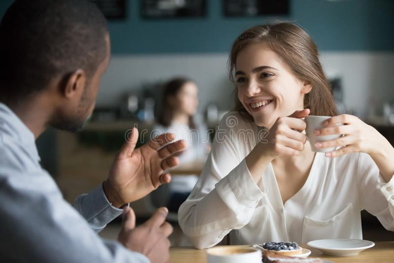 Happy diverse friends talk having fun meeting in cafe royalty free stock photo