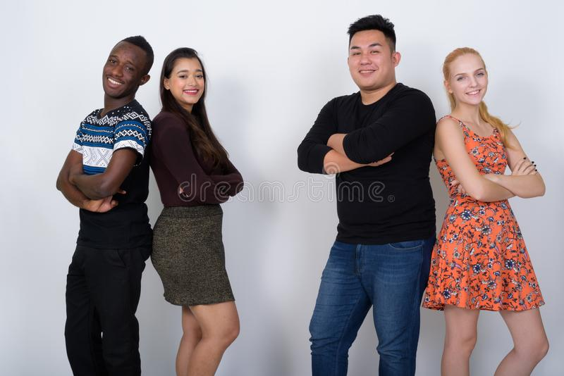 Happy diverse group of multi ethnic friends smiling with arms cr royalty free stock photos