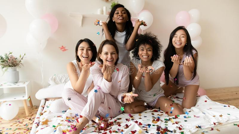 Happy diverse ladies wear pajamas sit on bed hold confetti royalty free stock photos