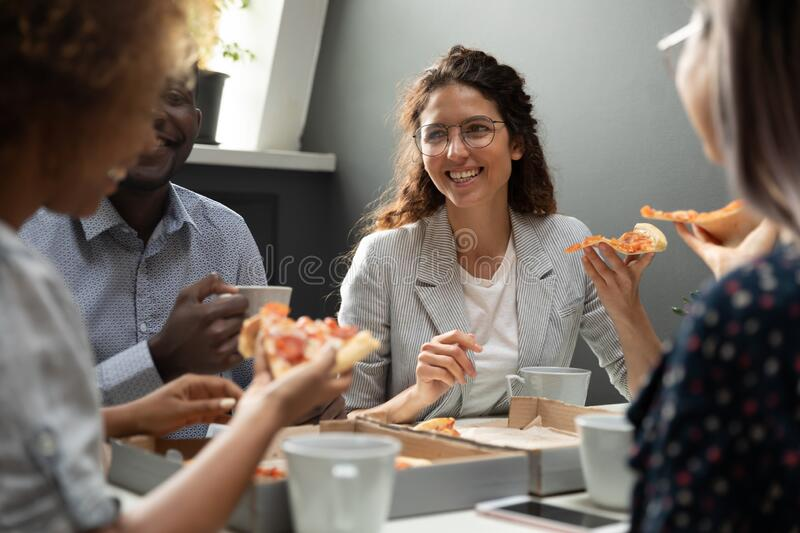 Smiling multiethnic colleagues have fun spending lunch break together stock photos