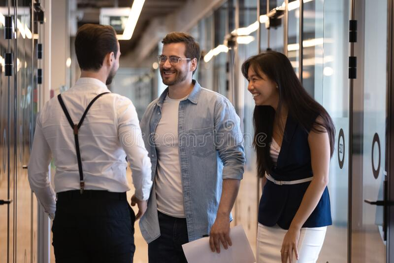 Happy multiethnic coworkers chatting in modern office corridor royalty free stock images