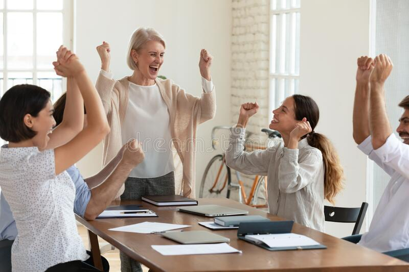 Happy multicultural colleagues celebrate business win in office royalty free stock photography