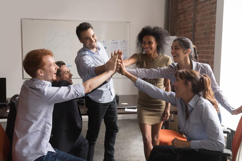 Happy diverse office employees group give high-five, corporate trust concept royalty free stock photo