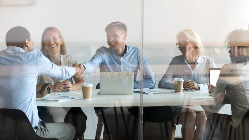 Happy diverse partners handshake at group meeting behind glass door stock photos