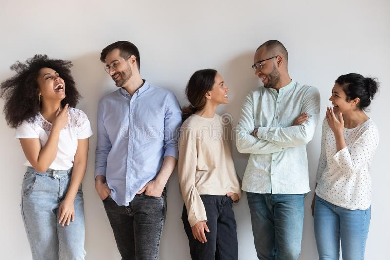 Happy diverse people having fun, talking, standing in row. Isolated on grey background, excited colleagues, students, friends discussing news, having pleasant royalty free stock images