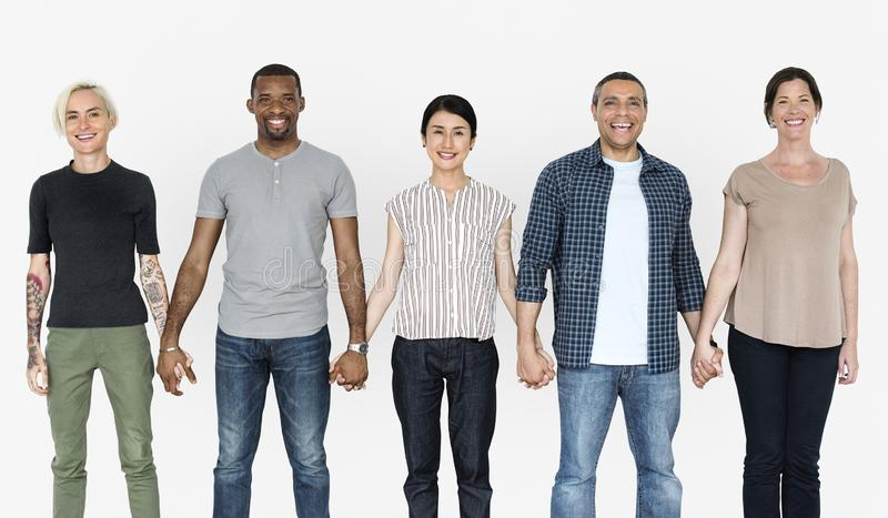 Happy diverse people holding hands together stock photo