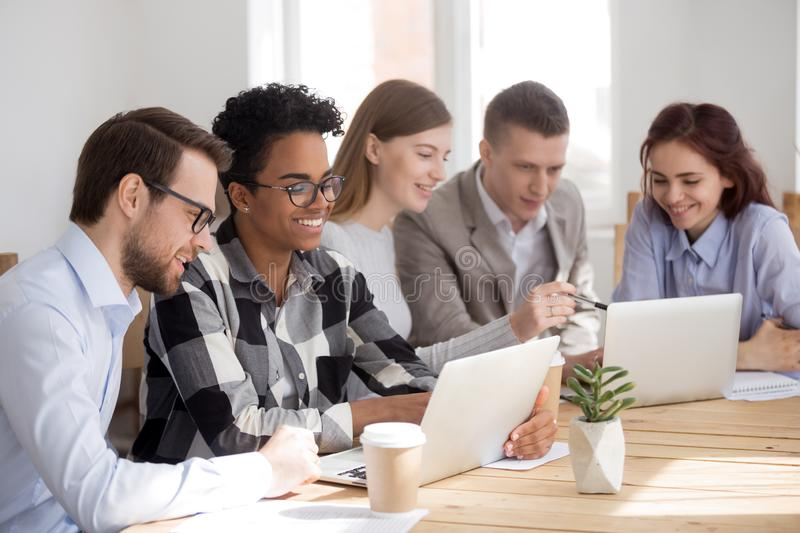 Happy diverse research team working on laptops cooperating brainstorming royalty free stock photography