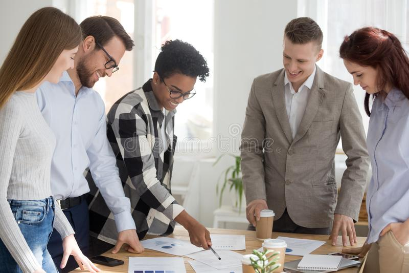 Happy diverse team brainstorm in office with papers on table stock photos