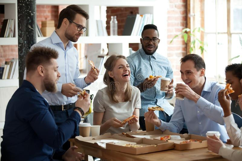 Happy diverse team people talking laughing eating pizza in office. Happy diverse team people talking laughing at funny joke eating ordered pizza in office royalty free stock photography