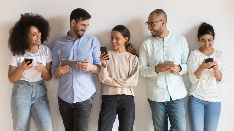 Happy diverse young people using different electronic devices. Happy diverse young people standing in row  on white background, using different electronic royalty free stock image