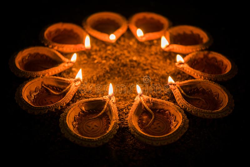 Happy Diwali and circle of Diya - many Terracotta diyas or oil lamps arranged over clay surface or ground in round or circular sha. Pe, selective focus stock photos
