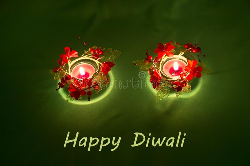 Happy Diwali. Traditional Indian festival green background with burning candles decorated with bright red flowers. Deepavali celeb royalty free stock photography