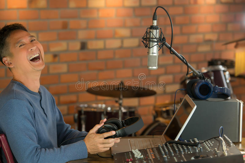 Happy DJ laughing while working on air at radio broadcasting . Male radio broadcaster using laptop computer and audio mixer controlling his live concert radio royalty free stock image