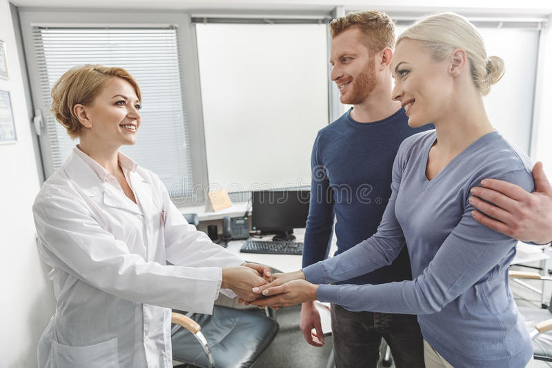 Happy doctor congratulating future parents royalty free stock images