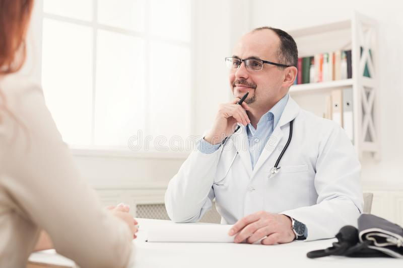 Happy doctor consulting woman in hospital royalty free stock image