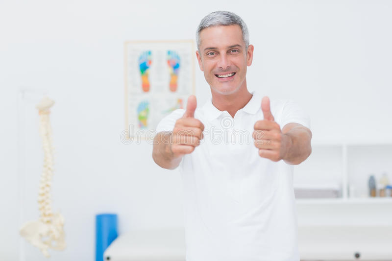 Happy doctor looking at camera with thumbs up royalty free stock images