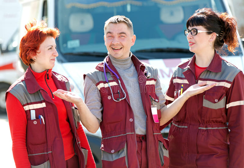 Happy doctor man gesturing with smiling paramedics coworker colleague stock images