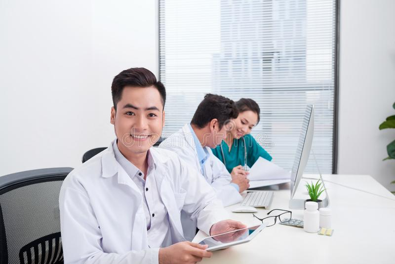 Happy doctor man with medical staff at the hospital sitting at office stock photos