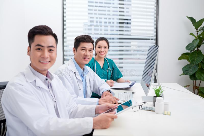 Happy doctor man with medical staff at the hospital sitting at office royalty free stock images