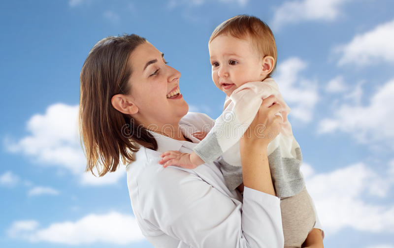 Happy doctor or pediatrician with baby over sky royalty free stock images