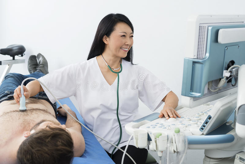 Happy Doctor Performing Ultrasound Test On Patient. Happy female doctor performing ultrasound test on male patient in hospital stock photo