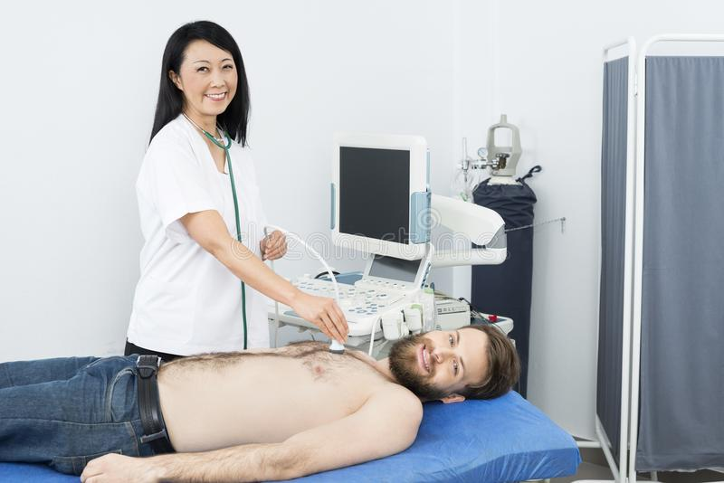 Happy Doctor Performing Ultrasound Test On Patient. Portrait of happy female doctor performing ultrasound test on male patient in hospital royalty free stock photography