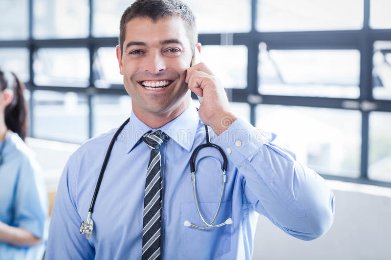 Happy doctor on the phone. In the hospital royalty free stock image
