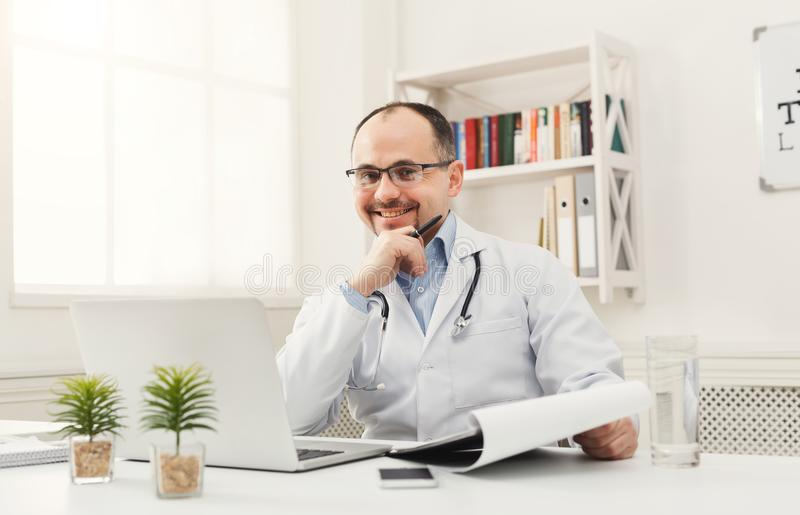 Happy doctor sitting in his office stock image