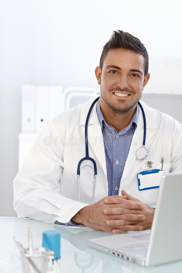 Download Happy Doctor Sitting At Desk Stock Images - Image: 26496264