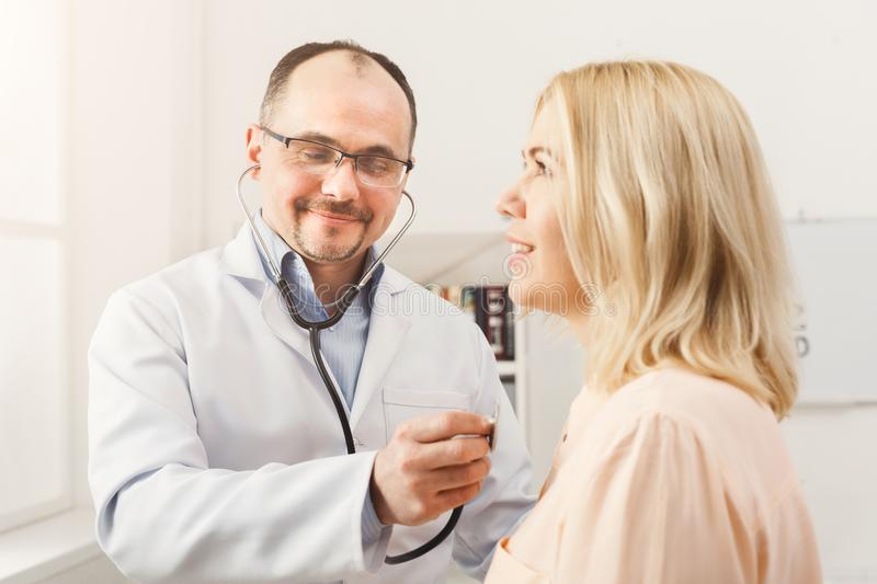 Doctor with stethoscope checking patient heart beat royalty free stock photos