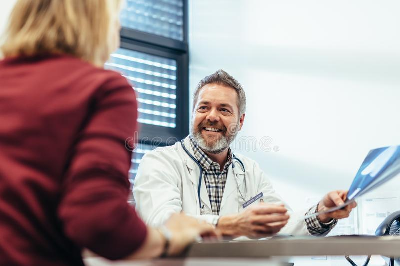 Happy doctor talking with patient in his office. Happy medical doctor showing diagnosis of x-ray image to female patient sitting at office desk. Doctor holding royalty free stock photo