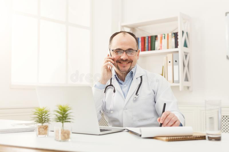 Happy doctor talking on the phone with his patient stock images
