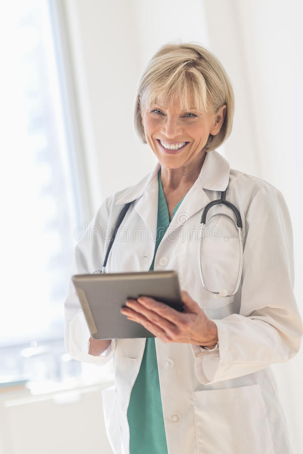 Happy Doctor Using Digital Tablet In Hospital stock photography