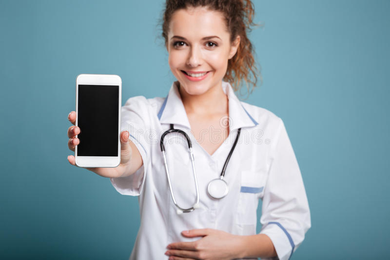 Happy doctor in white coat showing blank smartphone screen royalty free stock photo
