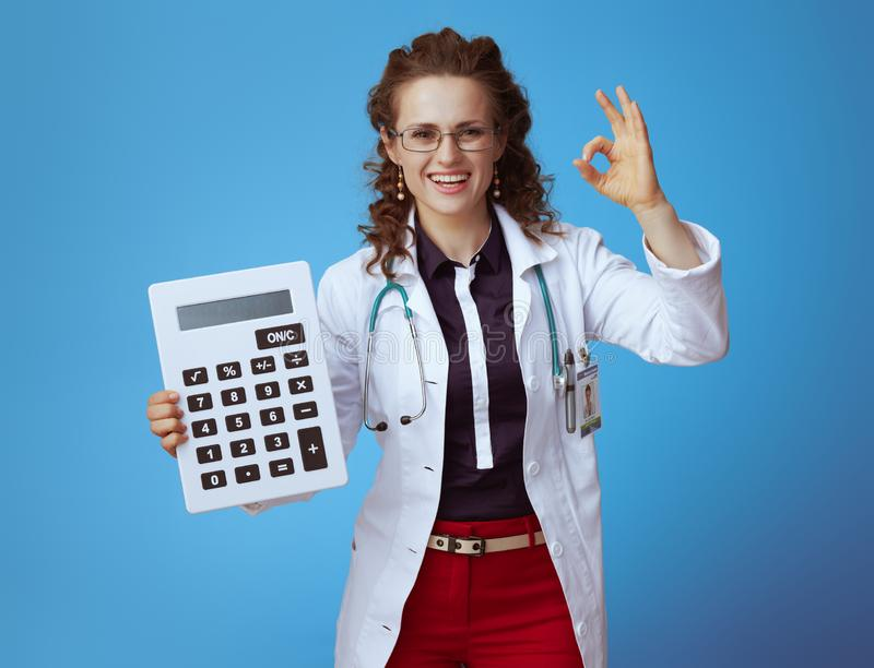 Happy doctor woman with big white calculator showing ok on blue. Happy elegant doctor woman in bue shirt, red pants and white medical robe with big white stock photo