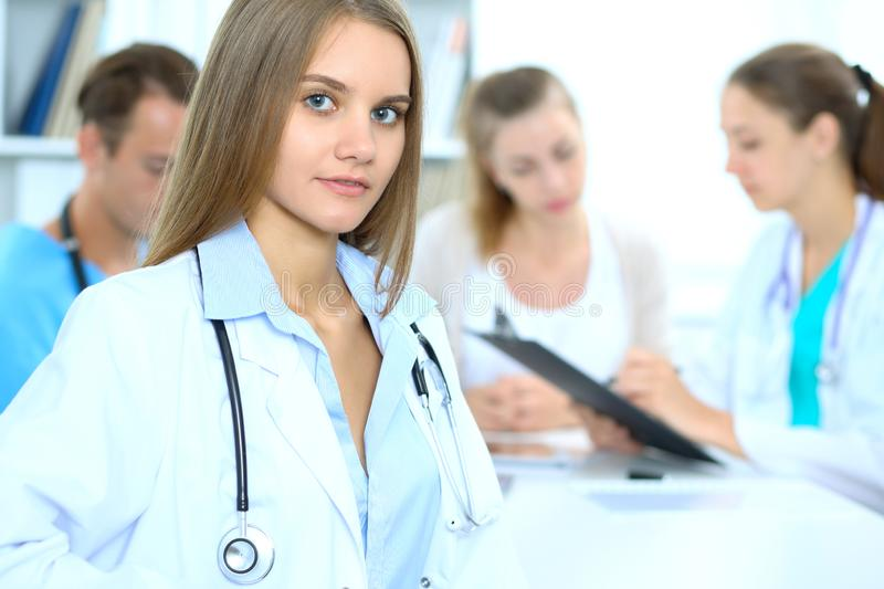 Happy doctor woman with medical staff at the background in hospital office royalty free stock photography