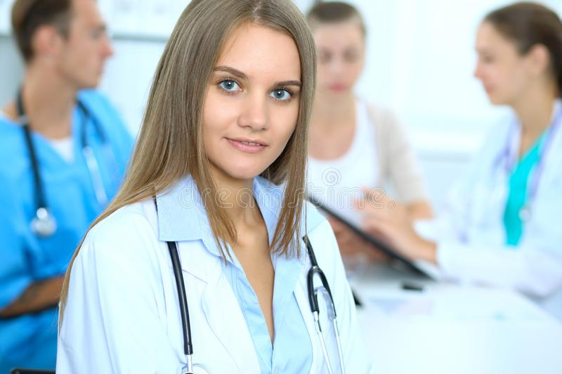 Happy doctor woman with medical staff at the background in hospital office royalty free stock image
