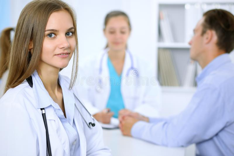 Happy doctor woman with medical staff at the background in hospital office stock photo