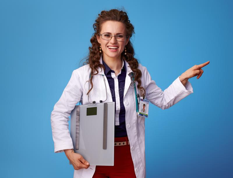 Happy doctor woman with scales pointing at something on blue stock photo