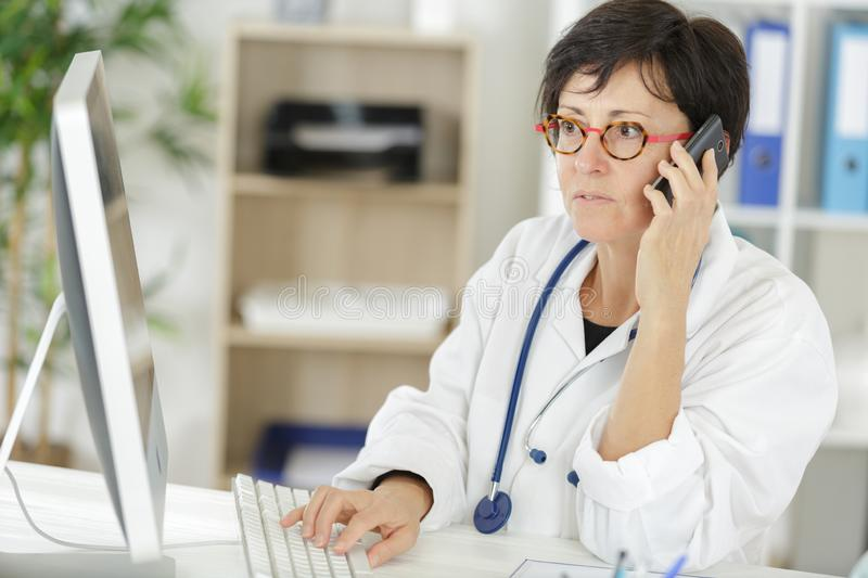 Happy doctor woman talking phone stock images