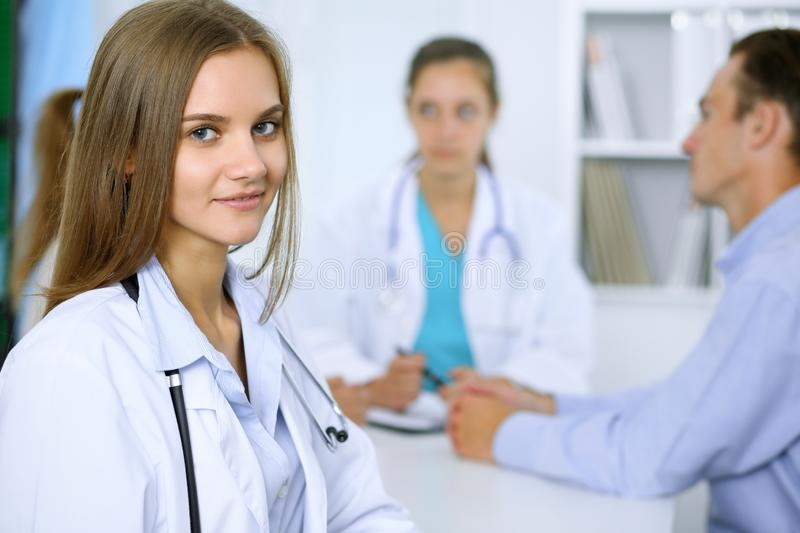 Happy doctor woman with medical staff at the background in hospital office royalty free stock photos