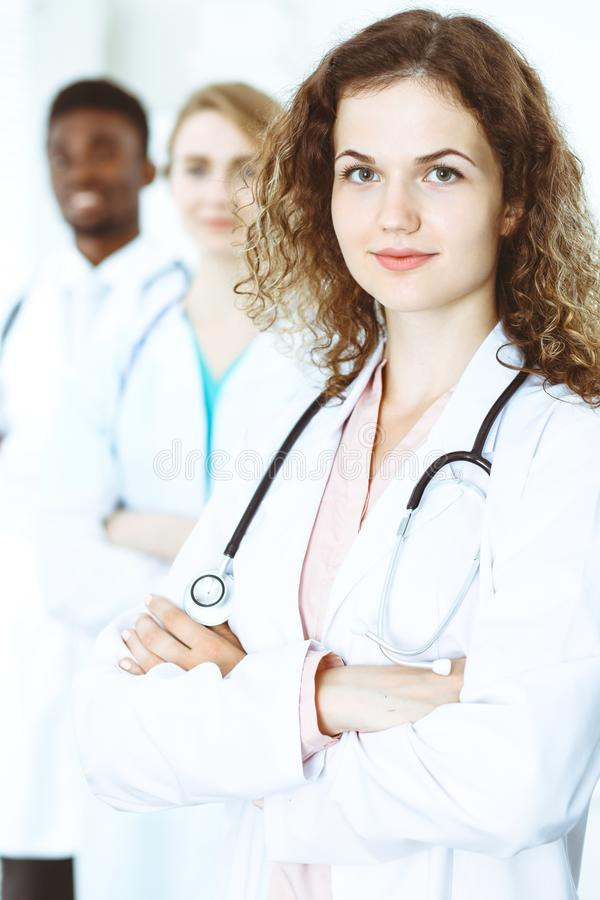 Happy doctor woman with medical staff at the hospital. Multi ethnic people group royalty free stock photos