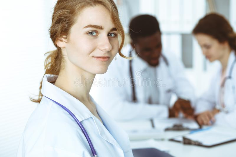 Happy doctor woman with medical staff at the hospital. Multi ethnic people group royalty free stock photo