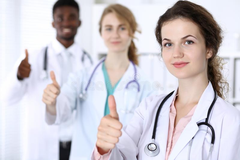 Happy doctor woman showing Ok sign with medical staff at the hospital. Multi ethnic people group royalty free stock image