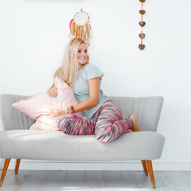 Happy domestic woman sitting on sofa indoors royalty free stock photos