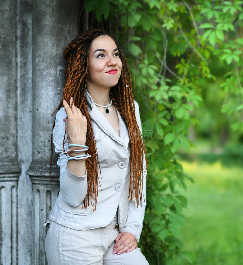 Happy dreadlocks fashionable girl posing near old column and trees royalty free stock images