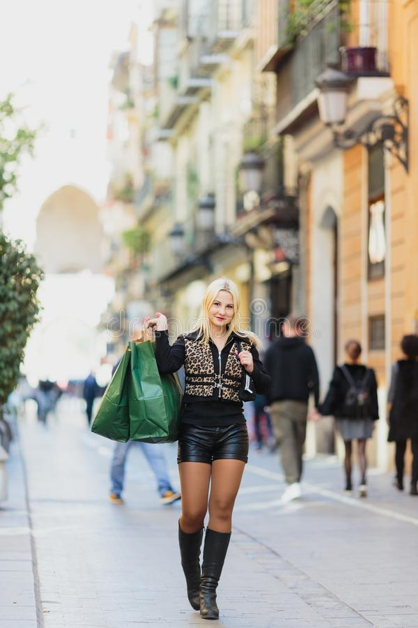 Happy dreaming Beautiful young blonde girl carrying two green paper packages royalty free stock photos