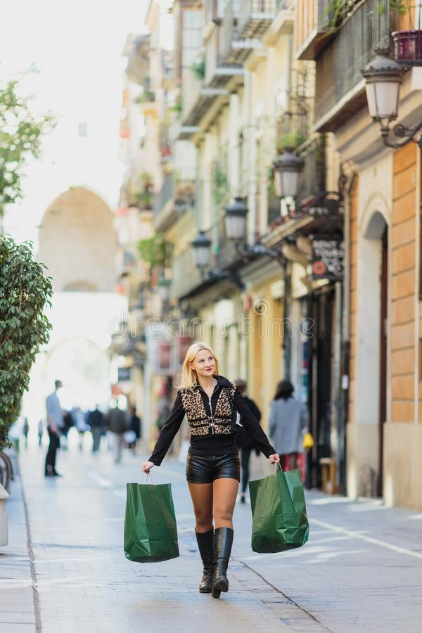 Happy dreaming Beautiful young blonde girl carrying two green paper packages stock photos