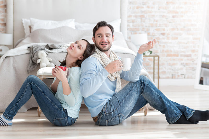 Happy dreamy couple sitting on the floor stock images