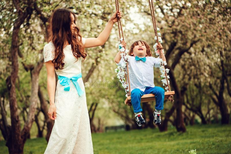 Happy dressy mother and toddler child son having fun on swing in spring or summer park. Wearing bow tie and long lacy dress for birthday or mothers day royalty free stock photo